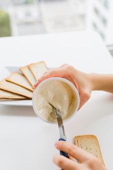 Il primo piano di una femmina che prende il formaggio si è sparso con il coltello per applicarlo sul pane sopra la tavola