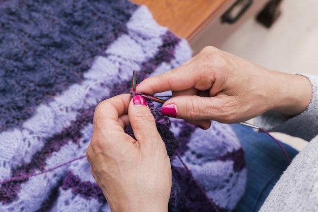 Il primo piano di una femmina passa a maglia la lana porpora