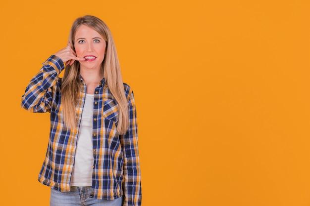 Il primo piano di una giovane donna che fa la chiamata gesture contro una priorità bassa arancione