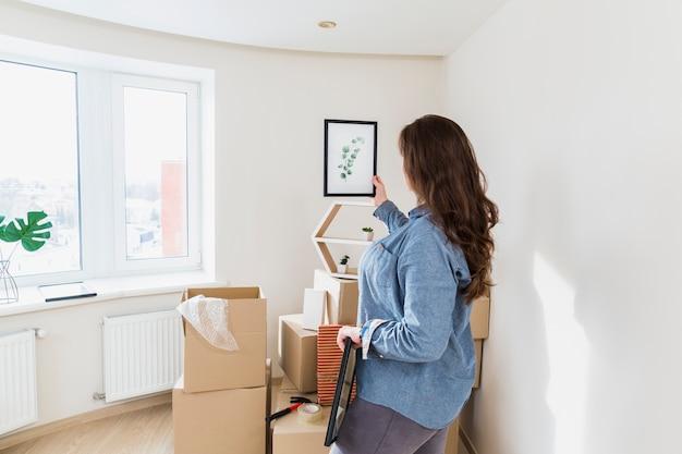 Il primo piano di una giovane donna che tiene lascia la cornice nella sua nuova casa