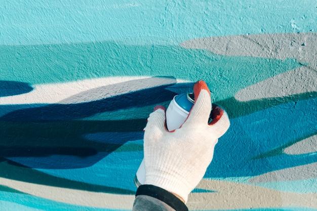 Il primo piano di una mano dell'uomo in un guanto tiene un pallone con pittura