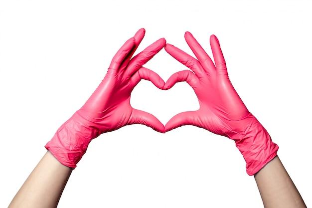 Il primo piano di una mano in guanti rosa medici di gomma del lattice ha piegato in un segno del cuore. isolato su sfondo bianco