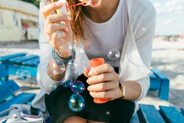 Il primo piano di una ragazza soffia le bolle sulla spiaggia