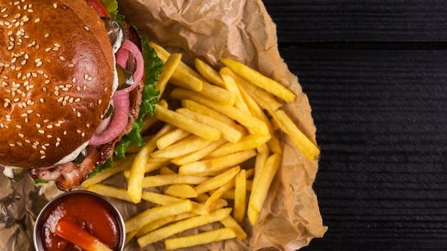 Il primo piano porta via l'hamburger con le patatine fritte e il ketchup