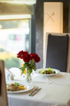 Il primo piano selettivo verticale ha sparato le rose rosse sulla tavola vicino ai piatti riempiti di alimento sulla tavola