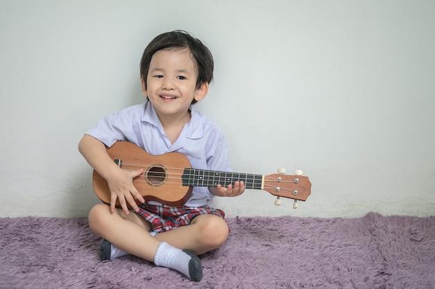 Il primo piano un bambino in ukulele del gioco dell'uniforme dello studente su tappeto con lo spazio della copia