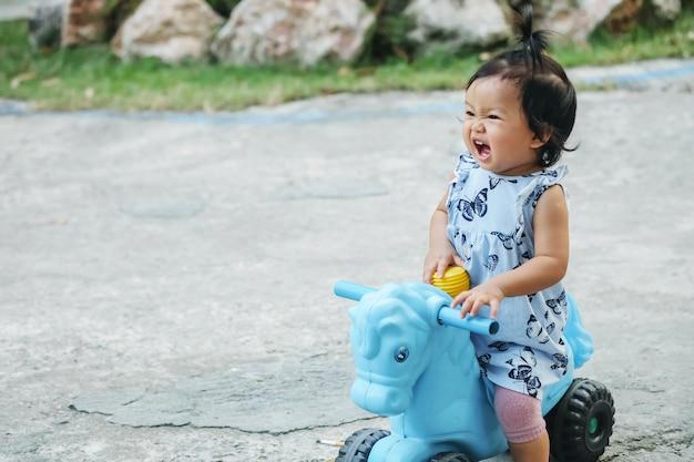 Il primo piano una bambina guida un giocattolo della bicicletta per il bambino con il fronte felice sul pavimento del cemento nel fondo strutturato del parco con lo spazio della copia