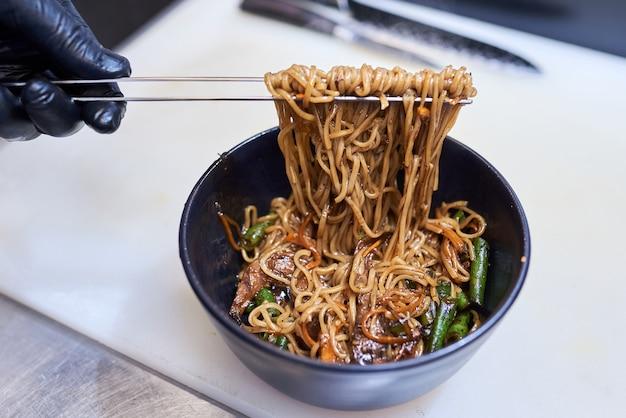 Il processo di cottura ha fritto le tagliatelle con le verdure nel wok, alimento asiatico tradizionale