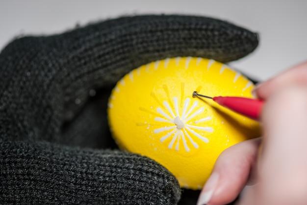 Il processo di dipingere le uova di pasqua con colorante alimentare e cera fusa. doppia verniciatura