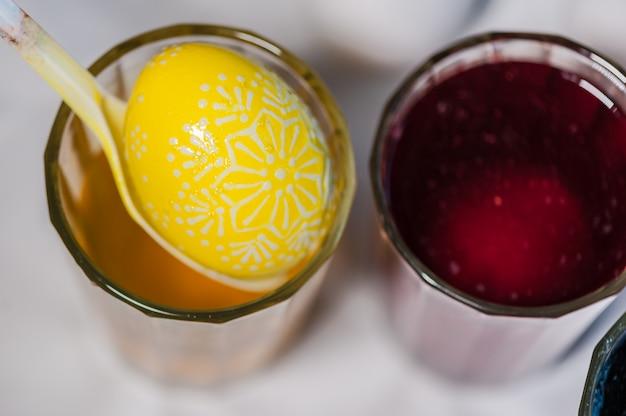 Il processo di dipingere le uova di pasqua con colorante alimentare e cera fusa. pronto.