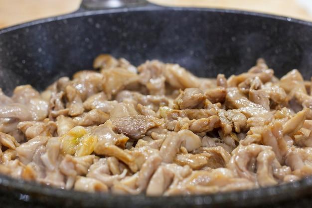 Il processo di frittura del filetto di pollo in una padella