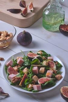 Il processo di preparazione dell'insalata con i fichi. insalata pronta e ingredienti su una tavola di legno bianca.