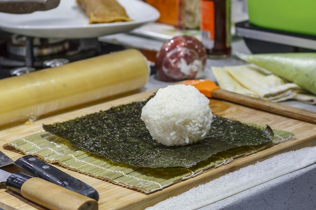Il processo di produzione di sushi e panini con cetriolo. riso su foglio nori