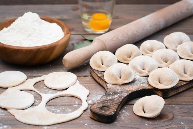 Il processo di stampaggio di gnocchi e ingredienti per cucinare su un tavolo di legno