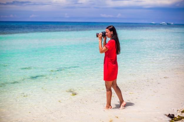 Il profilo di giovane donna ha fotografato la bella vista sul mare sulla spiaggia di sabbia bianca