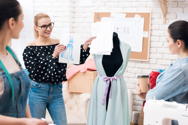 Il progettista dà schizzo agli assistenti per il vestito