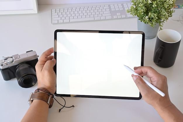 Il progettista del fotografo grafico pubblica la foto sulla compressa digitale nel luogo di lavoro