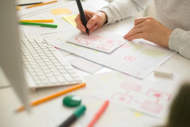 Il progettista di siti web crea un'applicazione di schizzo. sviluppare un progetto disegnando un mockup di interfaccia.