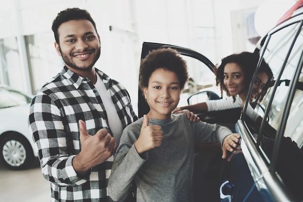 Il proprietario allegro dell'automobile di acquisto della famiglia mostra il pollice