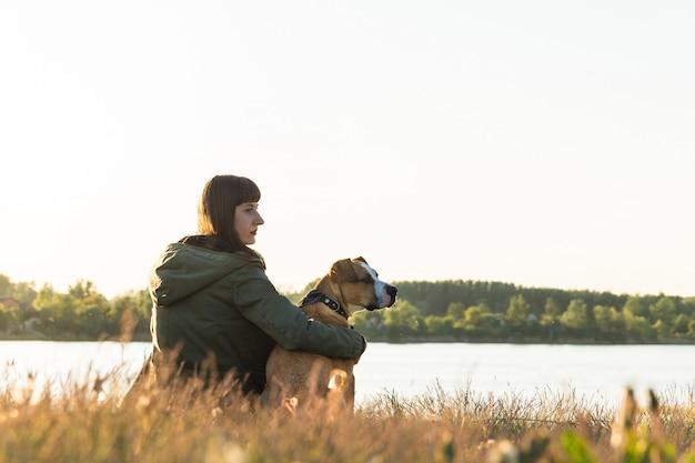 Il proprietario del cane e il suo animale domestico si siedono sulla riva del fiume al tramonto