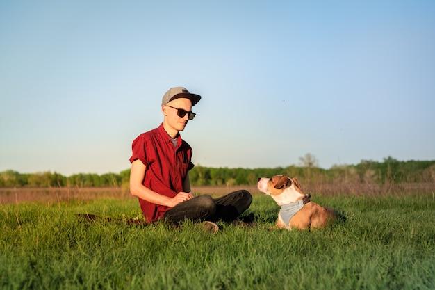 Il proprietario del cane maschio e lo staffordshire terrier addestrato si guardano l'un l'altro a prato