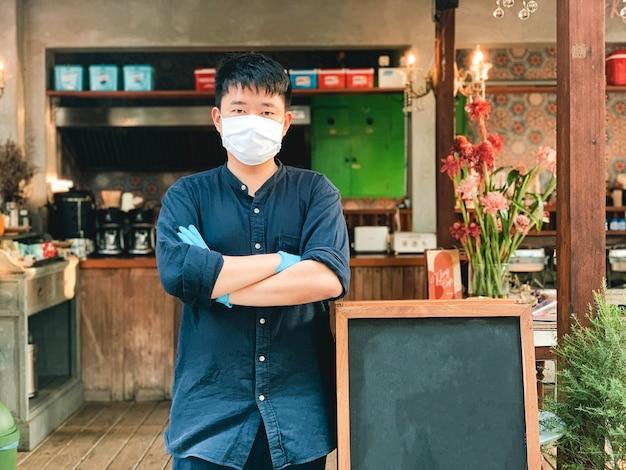 Il proprietario del negozio di cibo asiatico consegna cibo indossare maschera e guanti per la pulizia e l'igiene, proteggere da pandemia e epidemia covid-19 o virus corona.