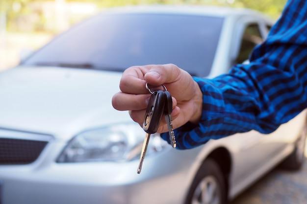 Il proprietario dell'auto è in piedi le chiavi dell'auto per l'acquirente. vendite di auto usate