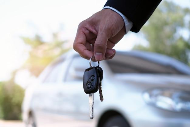 Il proprietario dell'auto è in piedi le chiavi dell'auto per l'acquirente.