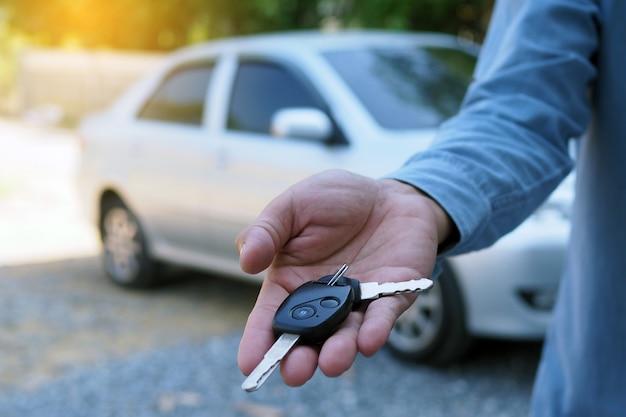 Il proprietario dell'auto è in piedi le chiavi della macchina per l'acquirente. vendite di auto usate