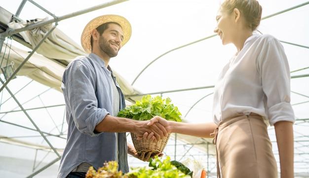 Il proprietario di un'azienda agricola biologica di ortaggi ha parlato con i clienti dell'attività di esportazione. stringi la mano quando parli con successo.