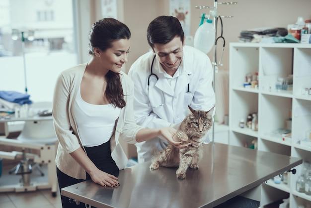Il proprietario felice dà l'alimento a cat woman holds tin can