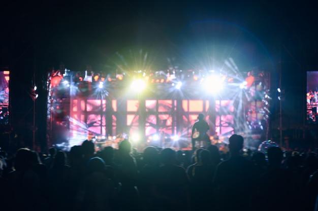 Il pubblico di giovani silhouette sta guardando il concerto notturno