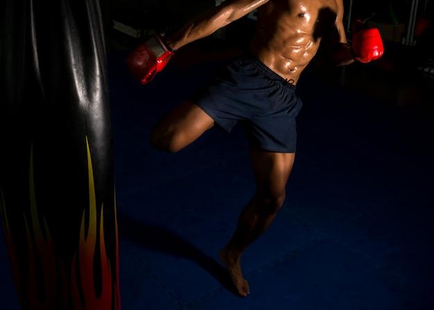 Il pugile calcia all'obiettivo sul ring in palestra