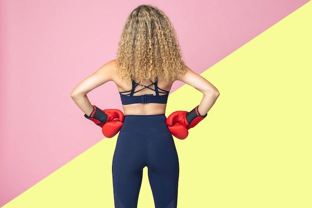Il pugile grazioso della donna dai capelli biondi e vestito in abiti sportivi sta sorridendo felicemente su un isolato di due colori rosa e gialli