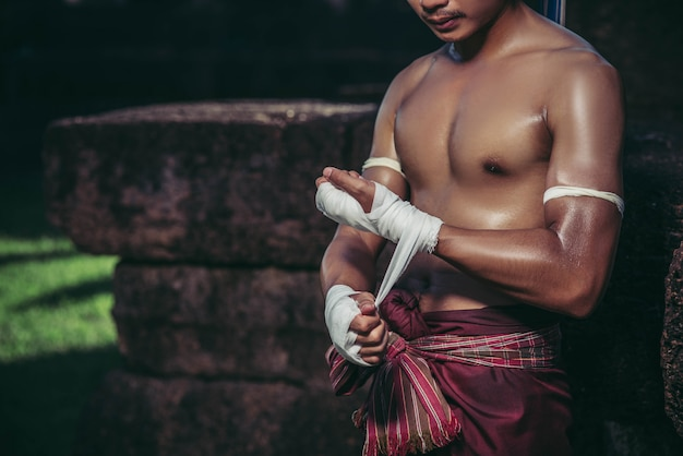 Il pugile si sedette sulla pietra, si legò il nastro intorno alla mano, preparandosi a combattere.