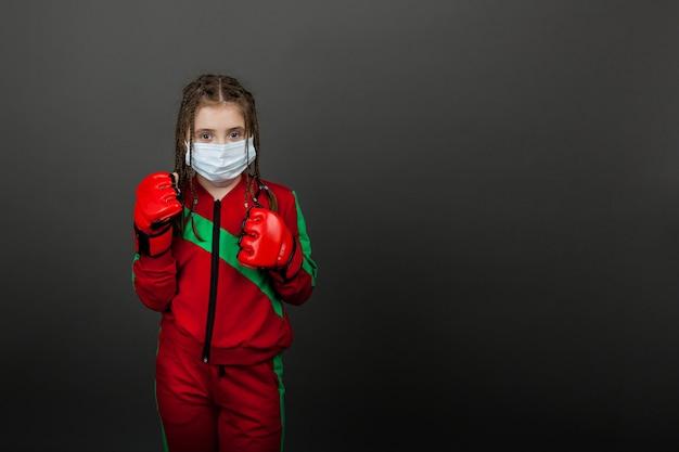 Il pugile sveglio della ragazza in maschera medica e guantoni da pugile sta stando in uno scaffale di pugilato.