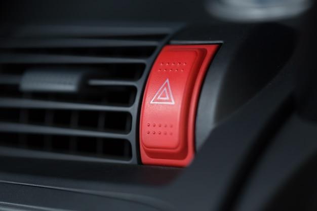 Il pulsante rosso di emergenza dell'automobile con il triangolo firma dentro il cruscotto del veicolo per l'autista