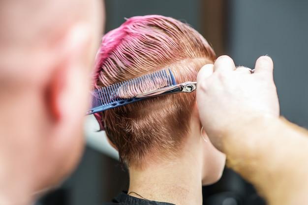 Il punto di vista posteriore del primo piano del parrucchiere sta tagliando i capelli rosa del cliente in salone.