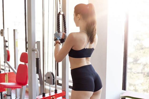 Il punto di vista posteriore della ragazza sportiva esile che indossa gli abiti sportivi, che posa all'indietro mentre si allena sulla stazione di forma fisica, facendo gli esercizi per il tricipite e la schiena, conduce lo stile di vita sano.