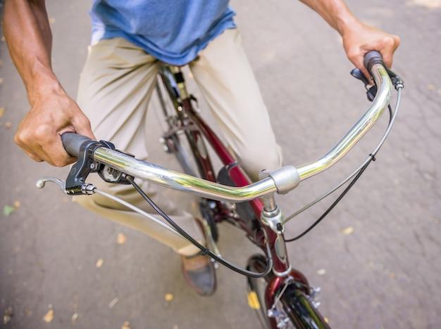 Il punto di vista superiore del primo piano dell'uomo senior sta guidando la bicicletta in parco.