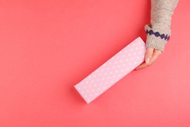 Il punto di vista superiore della donna passa il contenitore di regalo della tenuta su fondo rosa