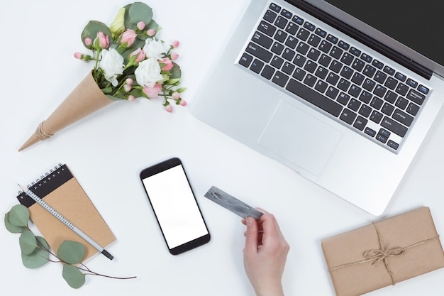 Il punto di vista superiore della donna passa la tenuta della carta di credito, concetto online di compera della tecnologia