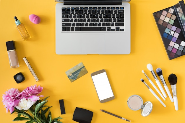 Il punto di vista superiore della donna passa la tenuta della carta di credito, il concetto online di acquisto, l'area di lavoro di bellezza con il computer portatile, il telefono cellulare, i fiori ed il taccuino, disposizione piana.