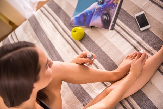 Il punto di vista superiore della donna sta verniciando le unghie dei piedi a casa.