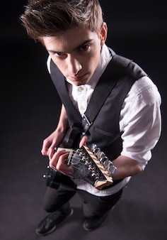 Il punto di vista superiore di giovane musicista maschio sta giocando.