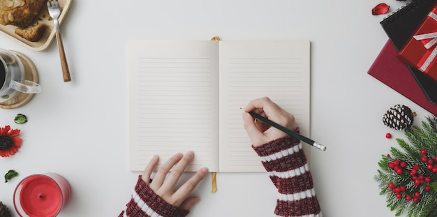 Il punto di vista superiore di scrittura della giovane donna sul taccuino nel natale ha decorato il posto di lavoro