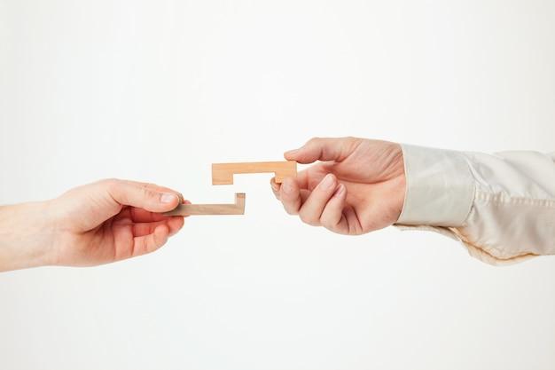 Il puzzle in legno giocattolo nelle mani solated su sfondo bianco
