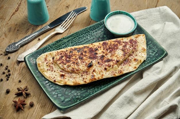 Il qutab è un piatto azero a base di pasta arrotolata sottilmente fritta con ripieni diversi con salsa allo yogurt in un piatto blu su un piatto di legno. chebureki