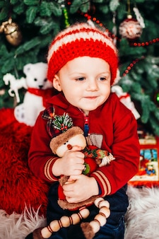 Il ragazzino abbraccia il suo piccolo giocattolo davanti a un albero di natale