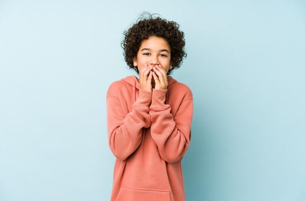 Il ragazzino afroamericano ha isolato la risata di qualcosa, coprendo la bocca di mani.